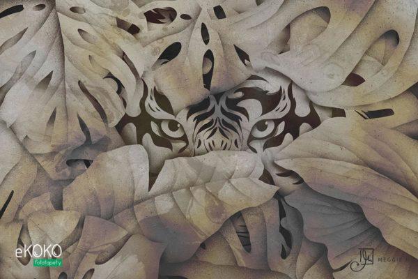 głowa tygrysa wyłaniająca się zza liści w beżowych odcieniach - fototapeta