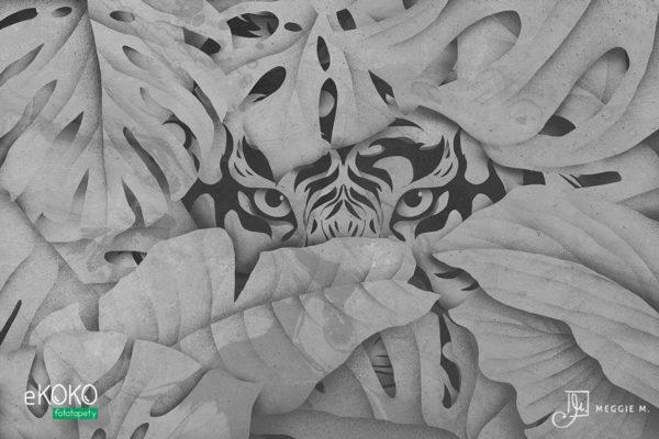 głowa tygrysa wyłaniająca się zza liści w szarych odcieniach - fototapeta